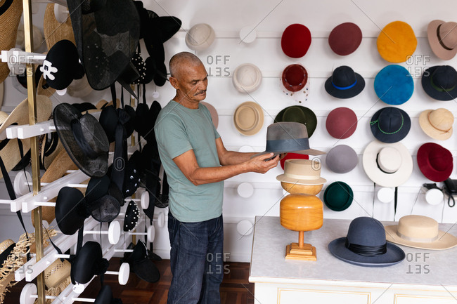 Side view of a senior mixed race man standing and inspecting a finished hat
