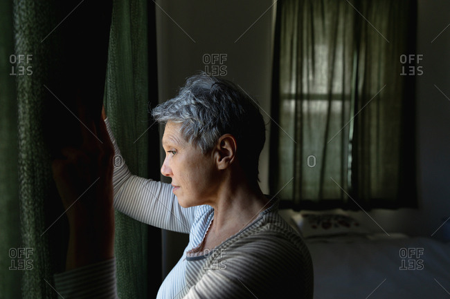 Side view close up of a mature Caucasian woman with short grey hair drawing the curtains and looking out of the window at home