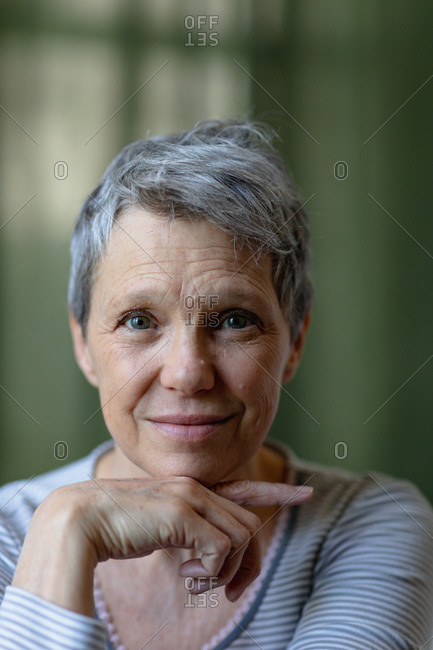 Portrait close up of a mature Caucasian woman with short grey hair looking straight to camera and smiling, with her chin resting on her hand