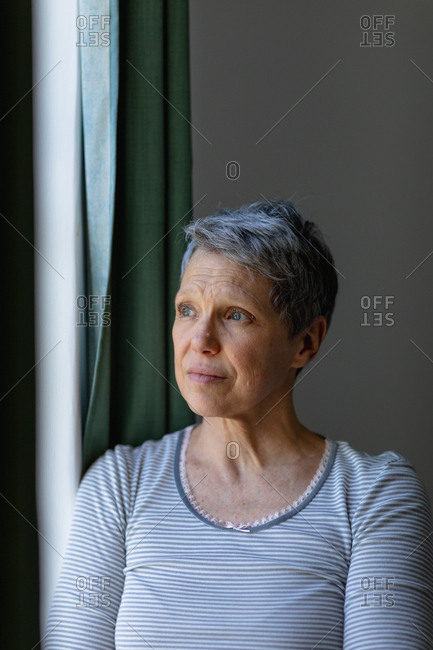 Front view close up of a mature Caucasian woman with short grey hair standing and looking out of the window at home