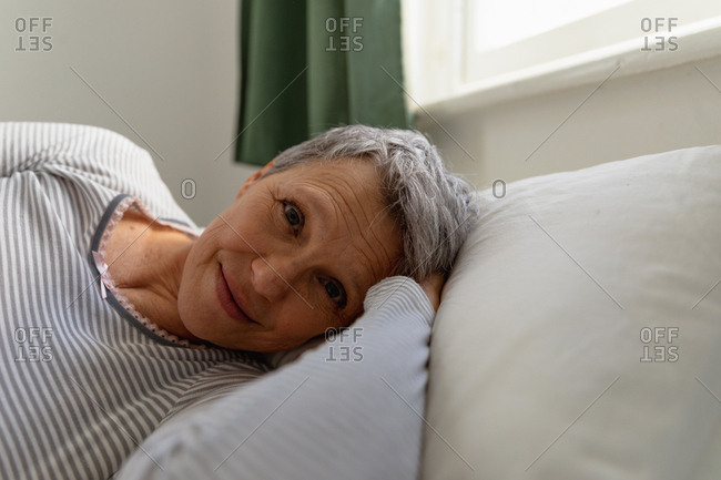 Front view close up of a mature Caucasian woman with short grey hair lying on her side in bed at home