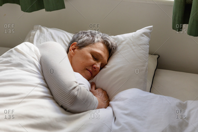Side view close up of a mature Caucasian woman with short grey hair lying on her side in bed at home sleeping