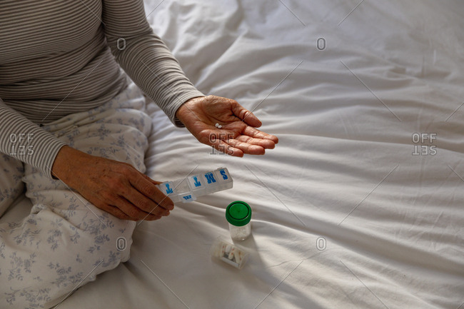 Front view mid section of a mature Caucasian woman sitting on her bed at home, holding two tablets and a weekly pill box