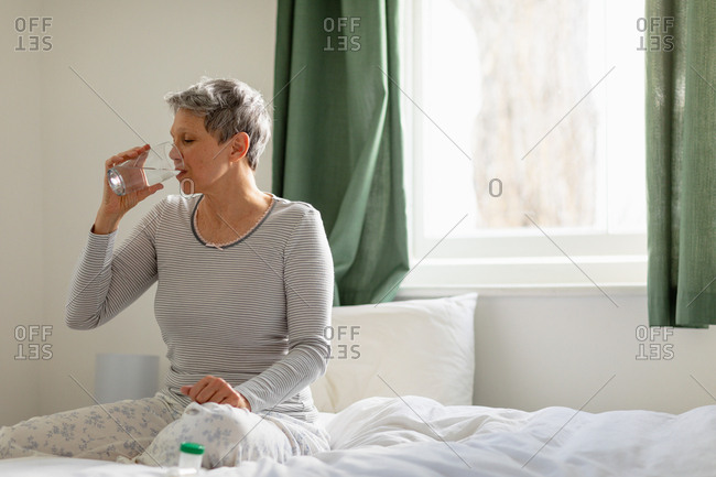 Front view of a mature Caucasian woman with short grey hair sitting on her bed at home drinking a glass of water and taking medication