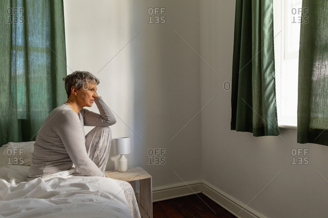 Side view of a mature Caucasian woman with short grey hair sitting on the side of her bed at home leaning on her raised knee, looking away