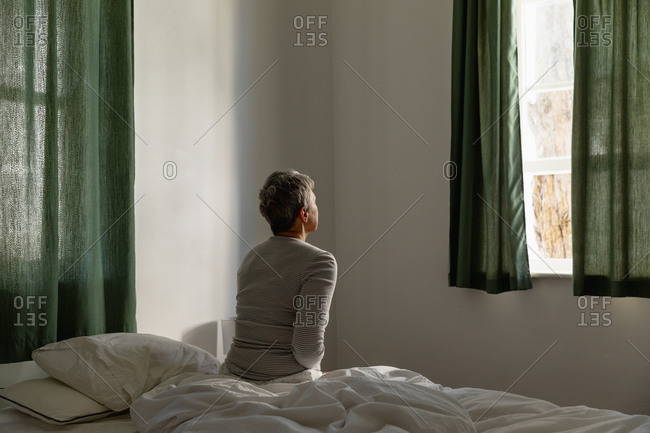 Rear view of a mature Caucasian woman with short grey hair sitting on the side of her bed at home looking out of the window