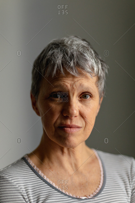 Portrait close up of a mature Caucasian woman with short grey hair looking straight to camera with an uncertain expression