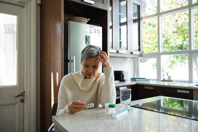 Front view of a mature Caucasian woman with short grey hair sitting in her kitchen looking at her medication
