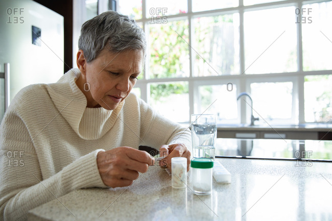 Side view close up of a mature Caucasian woman with short grey hair sitting in her kitchen looking at her medication