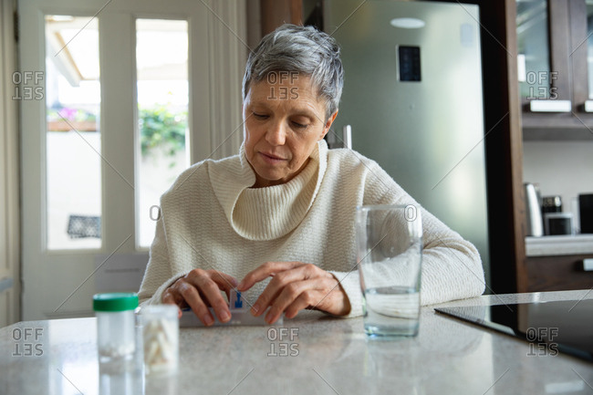 Front view close up of a mature Caucasian woman with short grey hair sitting in her kitchen looking at her medication