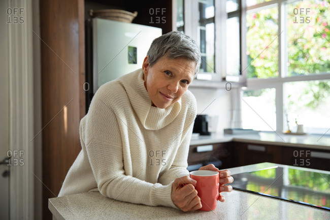 Portrait of a mature Caucasian woman with short grey hair sitting in her kitchen holding a cup of coffee and looking to camera smiling
