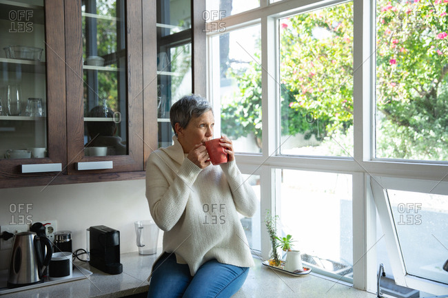 Front view of a mature Caucasian woman with short grey hair sitting on the counter in her kitchen drinking a cup of coffee and looking out of the window