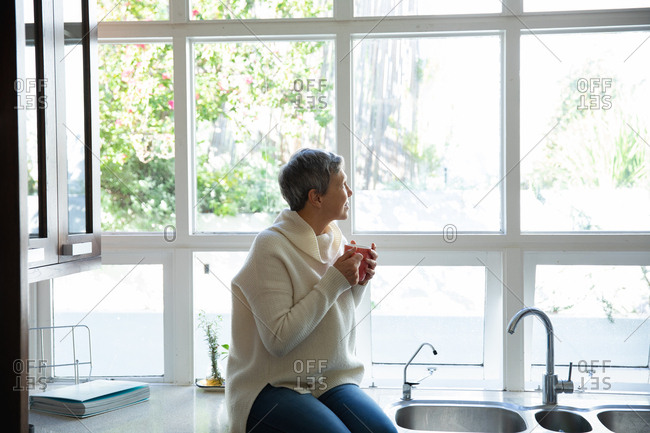 Side view of a mature Caucasian woman with short grey hair sitting on the counter in her kitchen holding a cup of coffee and looking out of the window