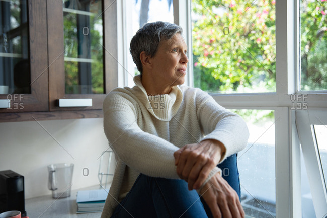 Side view close up of a mature Caucasian woman with short grey hair sitting on the counter in her kitchen looking out of the window