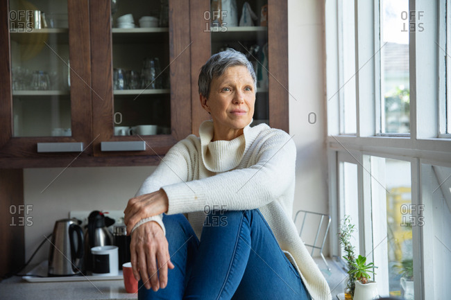 Front view close up of a mature Caucasian woman with short grey hair sitting on the counter in her kitchen looking out of the window