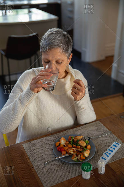 Elevated front view of a mature Caucasian woman sitting at her dining table drinking a glass of water