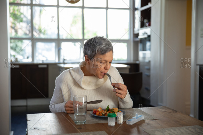 Front view of a mature Caucasian woman sitting and eating at her dining table, with a glass of water, bottles of tablets and a box of pills on the table in front of her