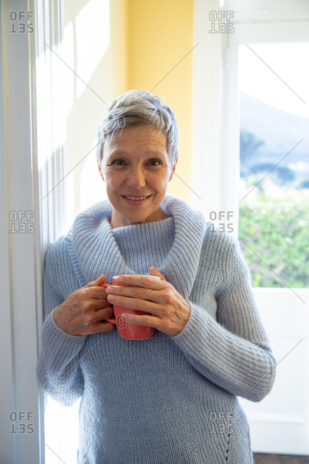 Portrait close up of a mature Caucasian woman with short grey hair wearing a cowl neck sweater, standing in front of a window at home holding a cup of coffee
