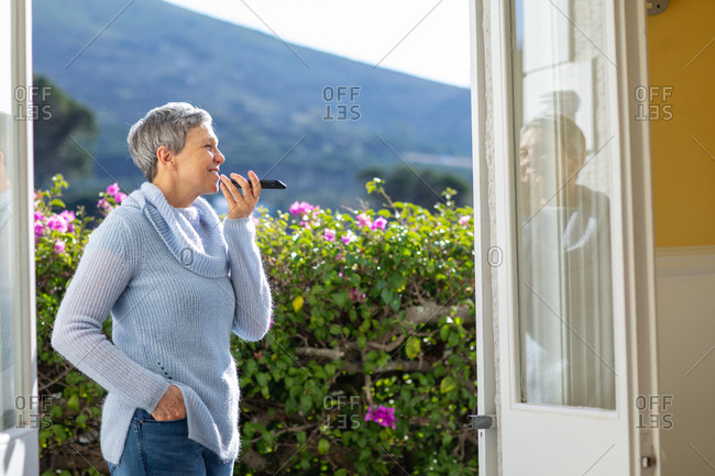 Side view of a mature Caucasian woman with short grey hair standing in her garden talking on a smartphone she is holding in front of her mouth and smiling