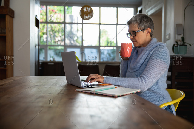 Side view close up of a mature Caucasian woman with short grey hair wearing glasses sitting at her dining room table holding a cup of coffee and using a laptop computer