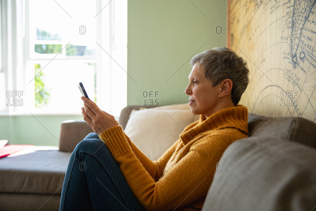 Side view close up of a mature Caucasian woman with short grey hair wearing a cowl neck sweater, sitting at home using a smartphone and smiling