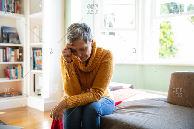 Front view close up of a mature Caucasian woman with short grey hair sitting at home in her living room looking down with her head leaning on her hand