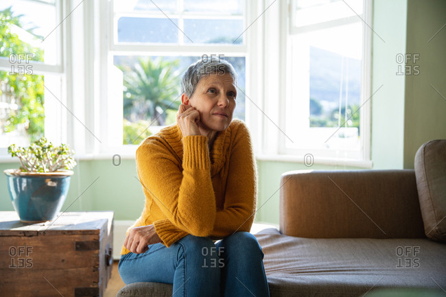 Front view close up of a mature Caucasian woman with short grey hair sitting on a sofa in her living room looking away with an uncertain expression
