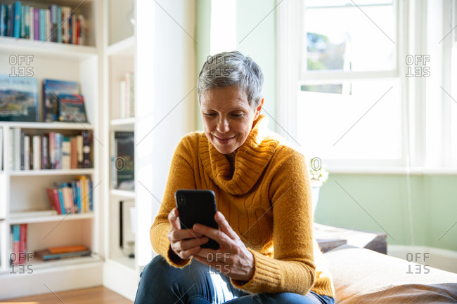 Front view close up of a mature Caucasian woman with short grey hair sitting at home in her living room using a smartphone