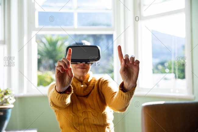 Front view close up of a mature Caucasian woman with short grey hair sitting at home in her living room wearing a VR headset