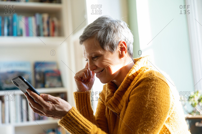 Side view close up of a mature Caucasian woman with short grey hair sitting at home in her living room smiling and using a smartphone