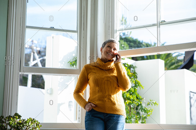 Front view of a mature Caucasian woman standing in front of the windows in her living room talking on a smartphone