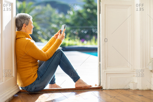 Side view close up of a mature Caucasian woman sitting in the doorway to the garden at home using a smartphone