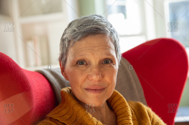Portrait close up of a mature Caucasian woman with short grey hair sitting in a red armchair in her living room looking to camera and smiling slightly