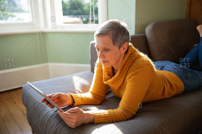 Side view close up of a mature Caucasian woman with short grey hair lying on her front on a sofa in her living room, leaning on her elbows and using a tablet computer