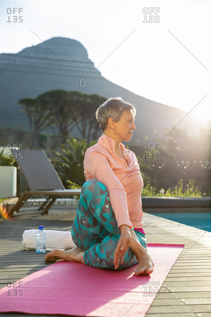 Side view close up of a mature Caucasian woman with short grey hair wearing sports clothes sitting on a mat in a yoga position, exercising by the swimming pool in her garden