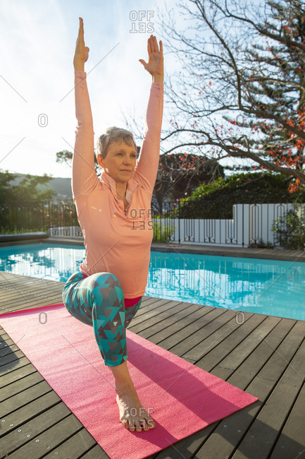 Front view close up of a mature Caucasian woman with short grey hair wearing sports clothes kneeling on a mat with arms raised in a yoga position, exercising by the swimming pool in her garden