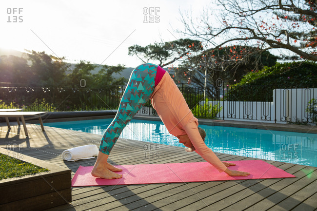 Side of a mature Caucasian woman with short grey hair wearing sports clothes standing bent over with her hands and feet on a mat in a yoga position, exercising by the swimming pool in her garden