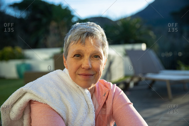 Portrait close up of a mature Caucasian woman with short grey hair sitting in her garden after exercising looking to camera and smiling slightly, with a towel on her shoulder