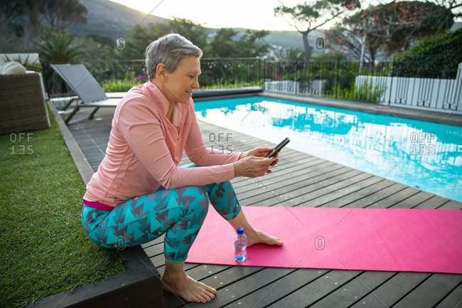 Side view of a mature Caucasian woman with short grey hair wearing sports clothes using a smartphone sitting by the swimming pool in her garden after a yoga workout