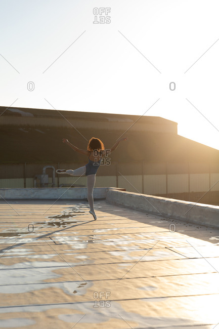 Rear view of a young mixed race female ballet dancer standing on her toes on one leg with her other leg and arms raised, on the rooftop of an urban building