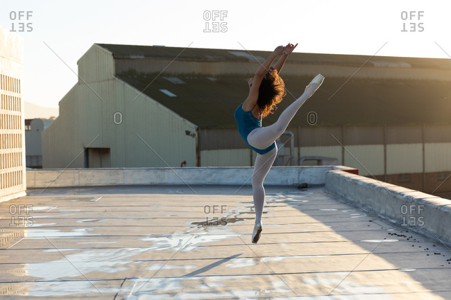 Side view of a young mixed race female ballet dancer jumping with her arms and one leg raised, on the rooftop of an urban building