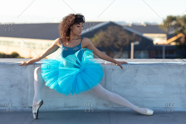 Front view of a young mixed race female ballet dancer wearing a blue tutu holding a ballet position and looking away on the rooftop of an urban building