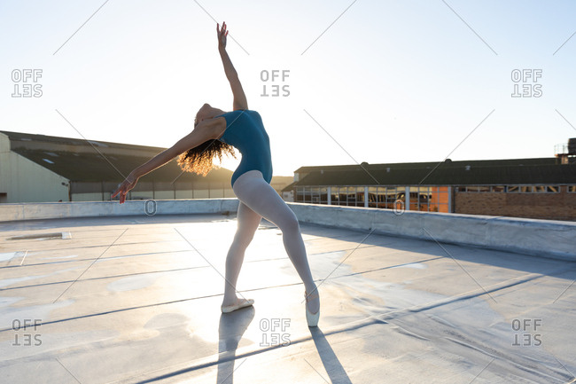 Side view of a young mixed race female ballet dancer leaning back in a ballet pose with arms outstretched, on the rooftop of an urban building