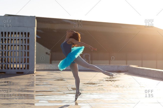 Side view of a young mixed race female ballet dancer wearing a blue tutu standing on one leg on her toes in a ballet pose, on the rooftop of an urban building