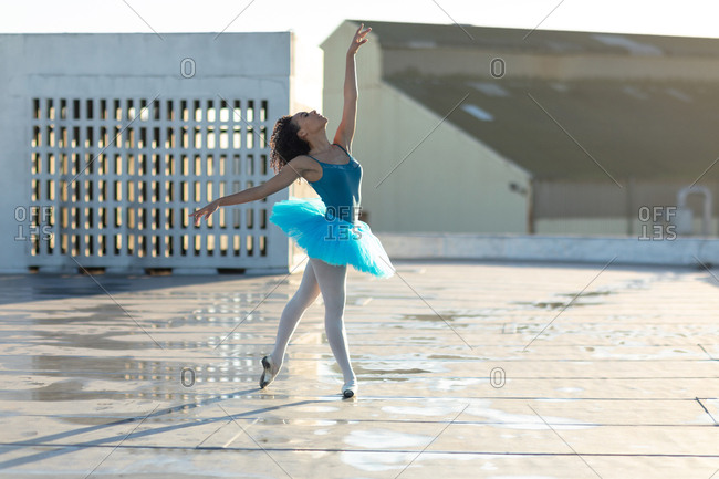 Side view of a young mixed race female ballet dancer wearing a blue tutu standing in a ballet pose with head back and one arm raised, on the rooftop of an urban building