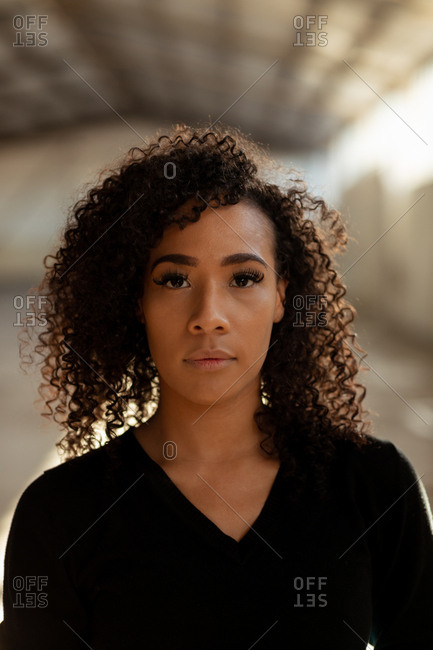Portrait close up of a young mixed race female ballet dancer with shoulder length curly hair looking straight to camera in an empty warehouse