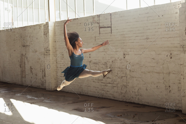 Side view of a young mixed race female ballet dancer leaping in the air with arms raised while dancing in an empty room at an abandoned warehouse