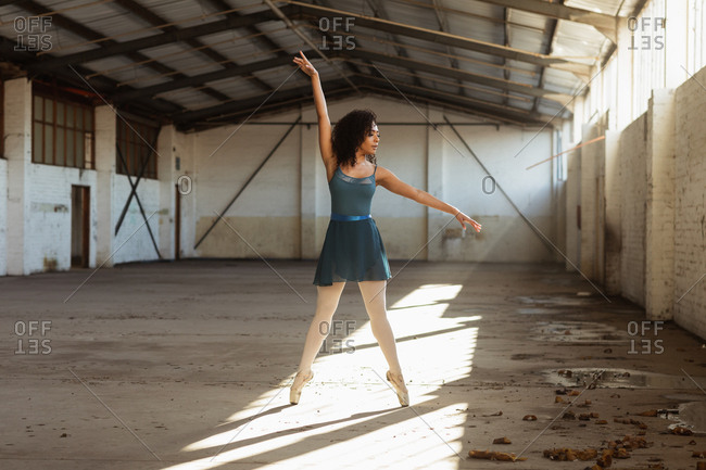Front view of a young mixed race female ballet dancer standing on her toes with arms raised in a shaft of sunlight while dancing in an empty room at an abandoned warehouse
