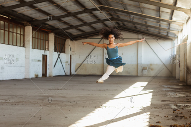 Front view of a young mixed race female ballet dancer leaping in the air with arms outstretched while dancing in an empty room at an abandoned warehouse
