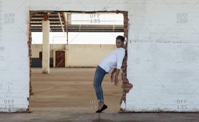 Side view of a young Caucasian male ballet dancer wearing jeans posing in a doorway in an empty room at an abandoned warehouse